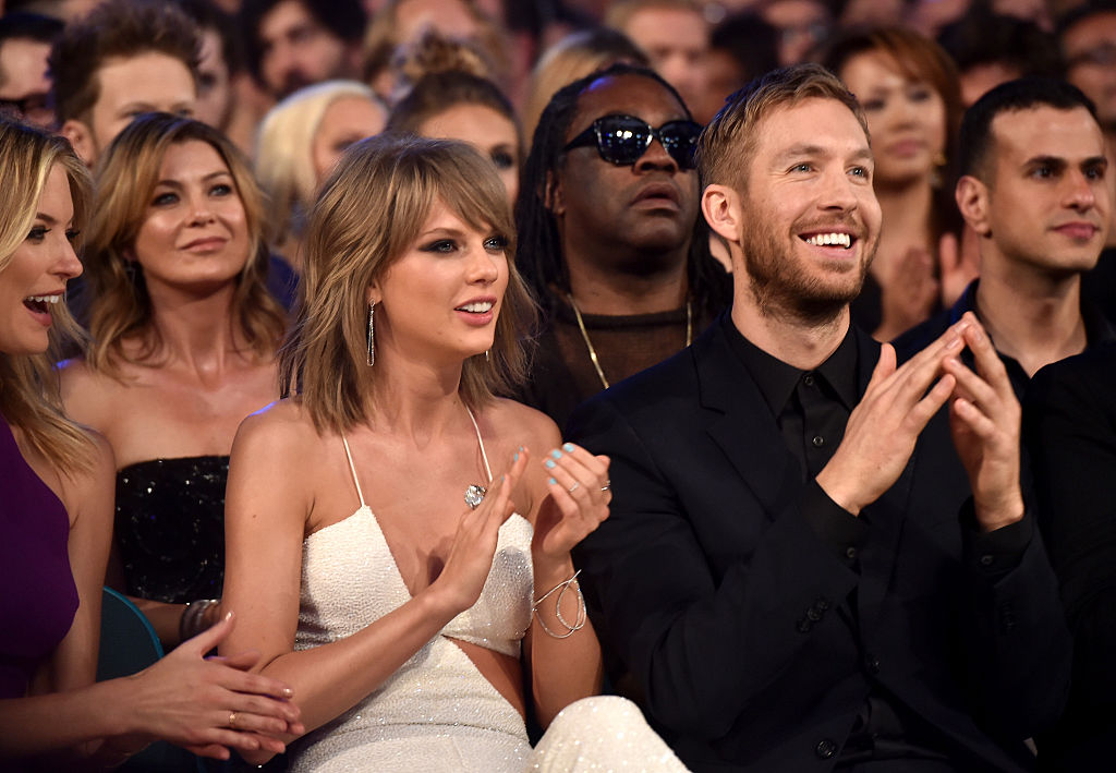 Taylor Swift and Calvin Harris smiling and clapping, sitting in a theater