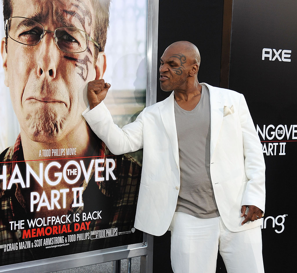 Mike Tyson posing next to a poster for 'The Hangover'