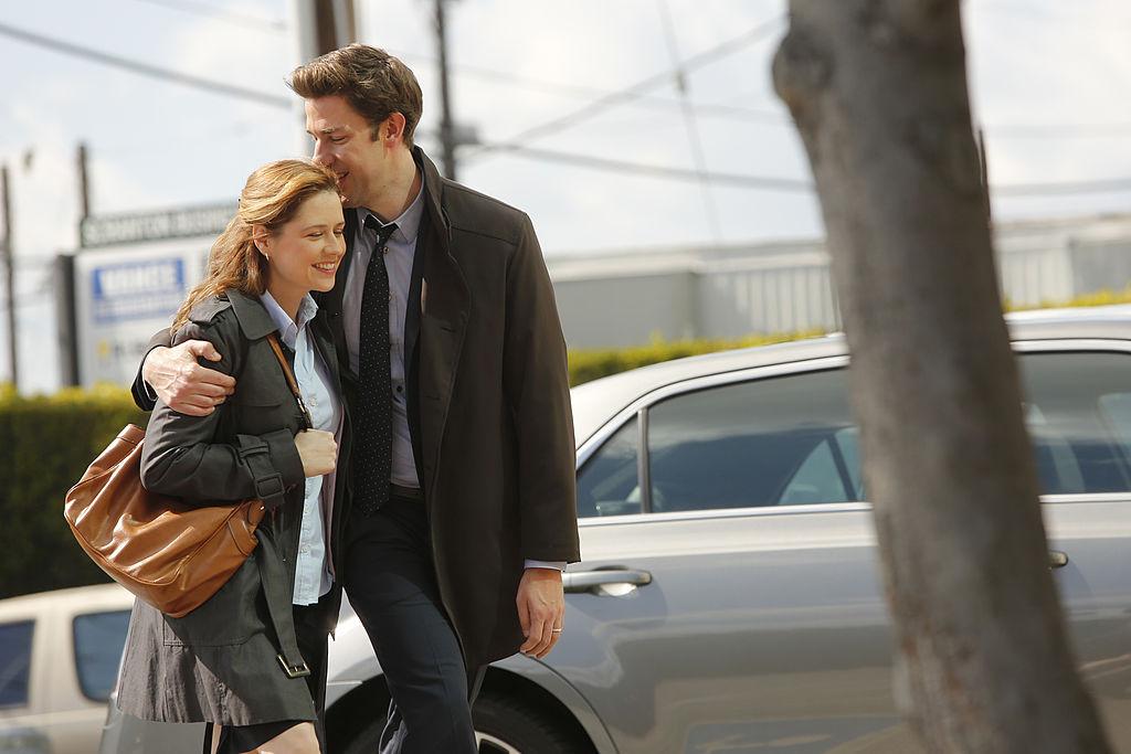 Jenna Fischer as Pam Beesly Halpert, John Krasinski as Jim Halpert embracing and smiling