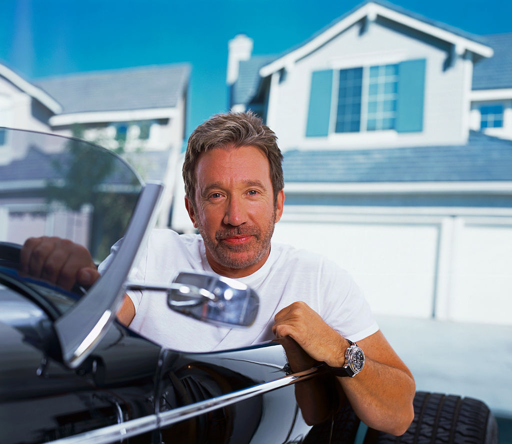 Tim Allen poses for a picture while sitting in a car