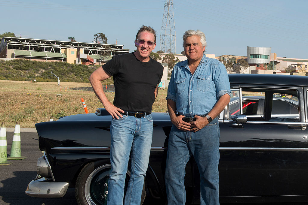 Tim Allen and Jay Leno standing outside smiling in front of a car