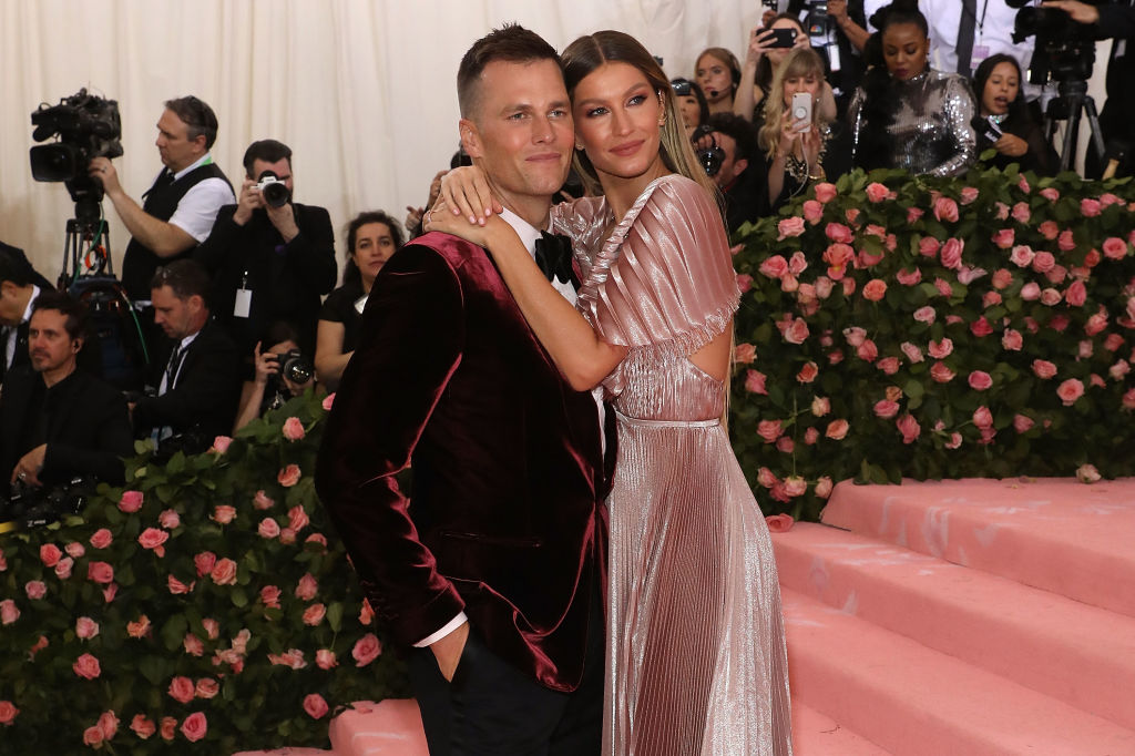 Tom Brady and Gisele Bundchen embracing, smiling at a camera to the side