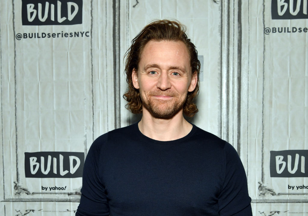 Tom Hiddleston smiling in front of a repeating background