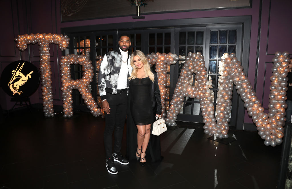 Tristan Thompson and Khloé Kardashian smiling in front of a balloon display