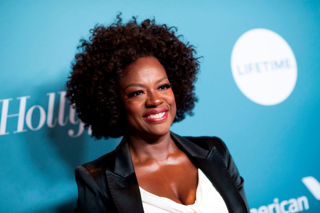 Viola Davis smiling in front of a repeating blue background