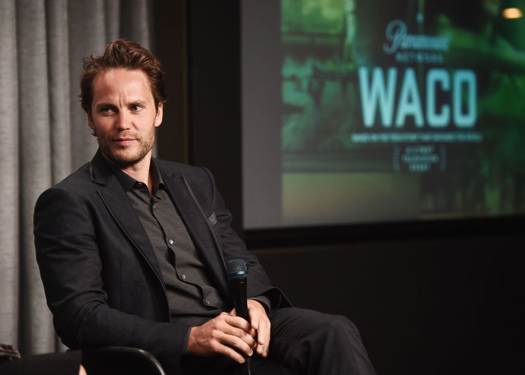 Taylor Kitsch seated holding a microphone in front of a 'Waco' screen