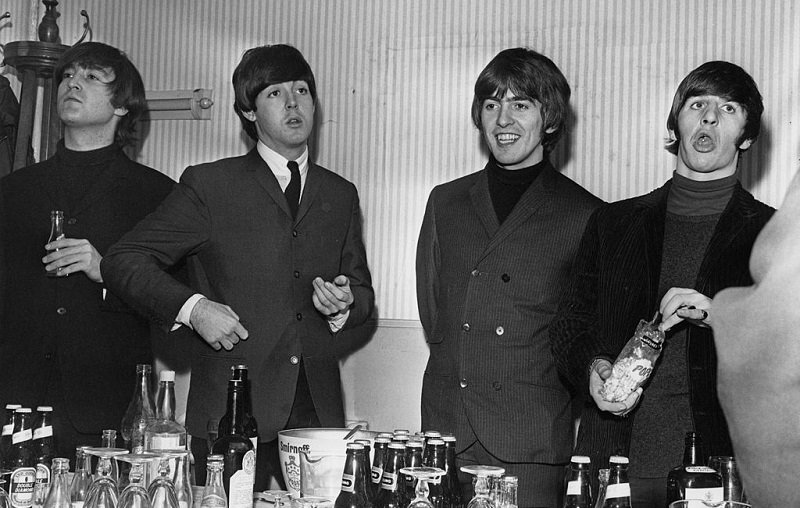 The Beatles at a table stocked with beer