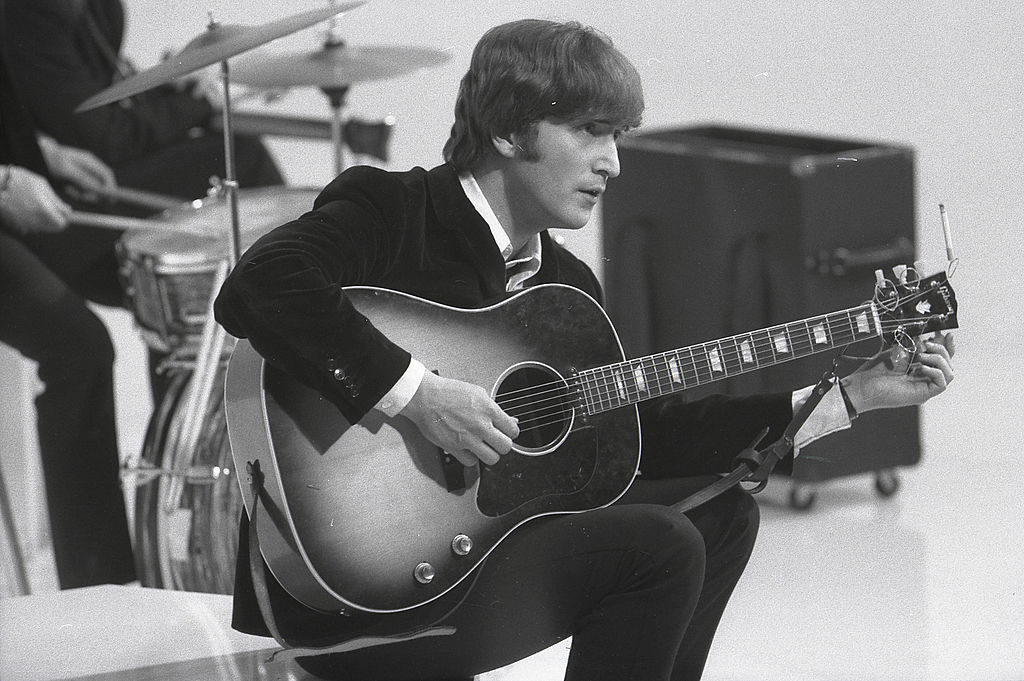 John Lennon of The Beatles sitting with his guitar