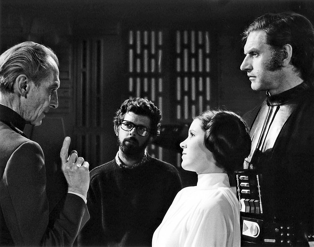 Peter Cushing, David Prowse, and Carrie Fisher with director, screenwriter, and producer George Lucas on the set of his movie 'Star Wars: Episode IV - A New Hope.'