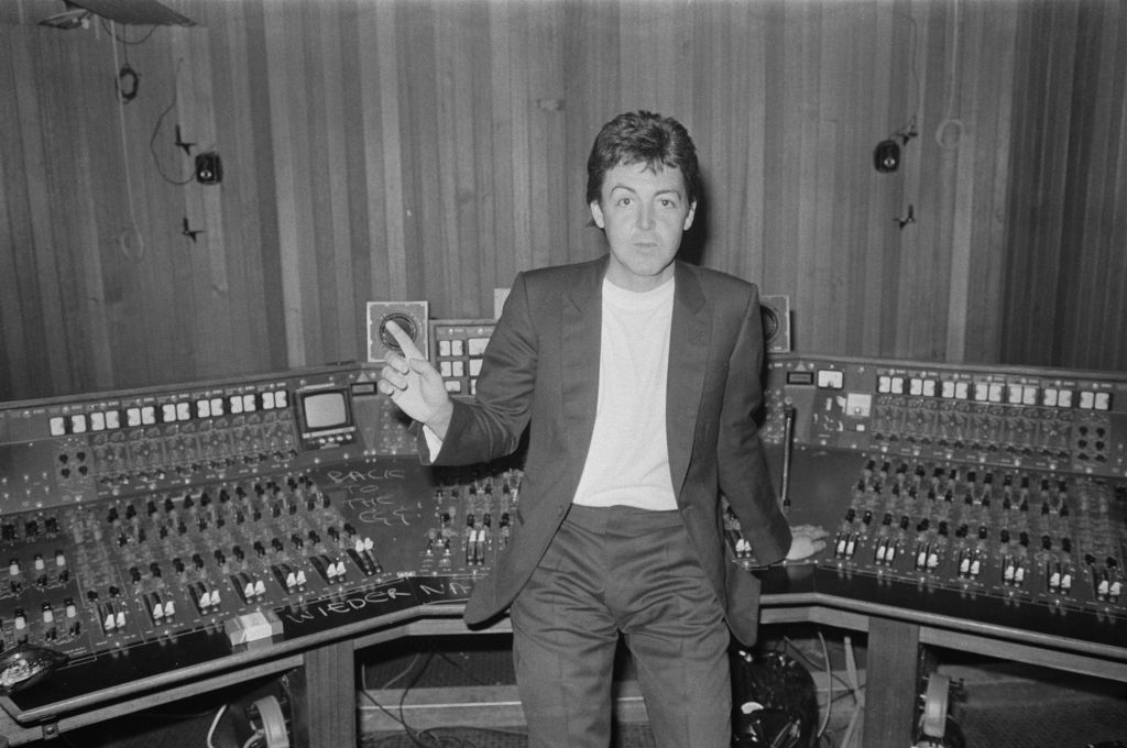 Paul McCartney in a recording studio pointing his finger at the ceiling