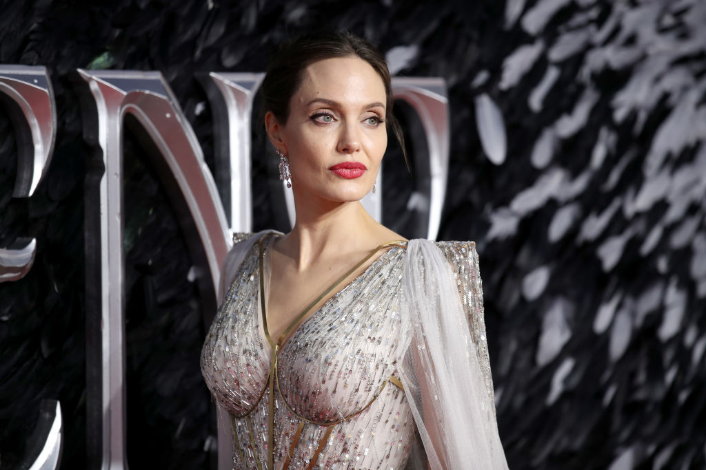 Angelina Jolie looking away from the camera in a light gray dress with beading
