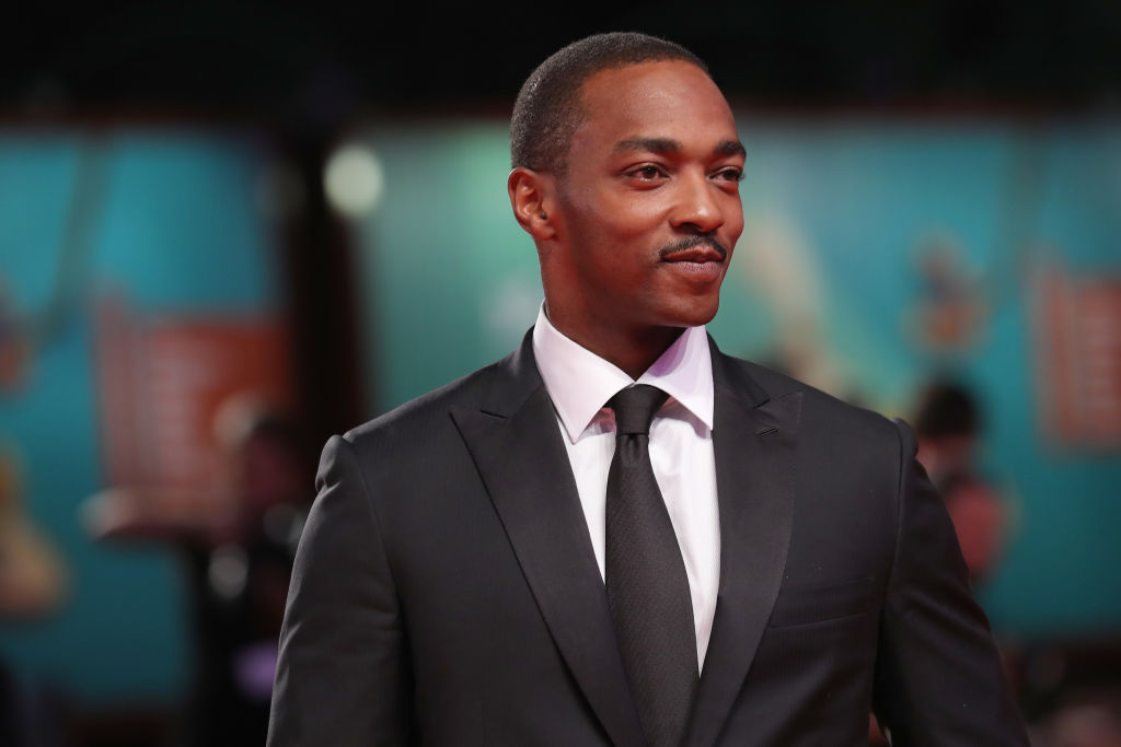 Anthony Mackie smiling, looking off camera, wearing a suit