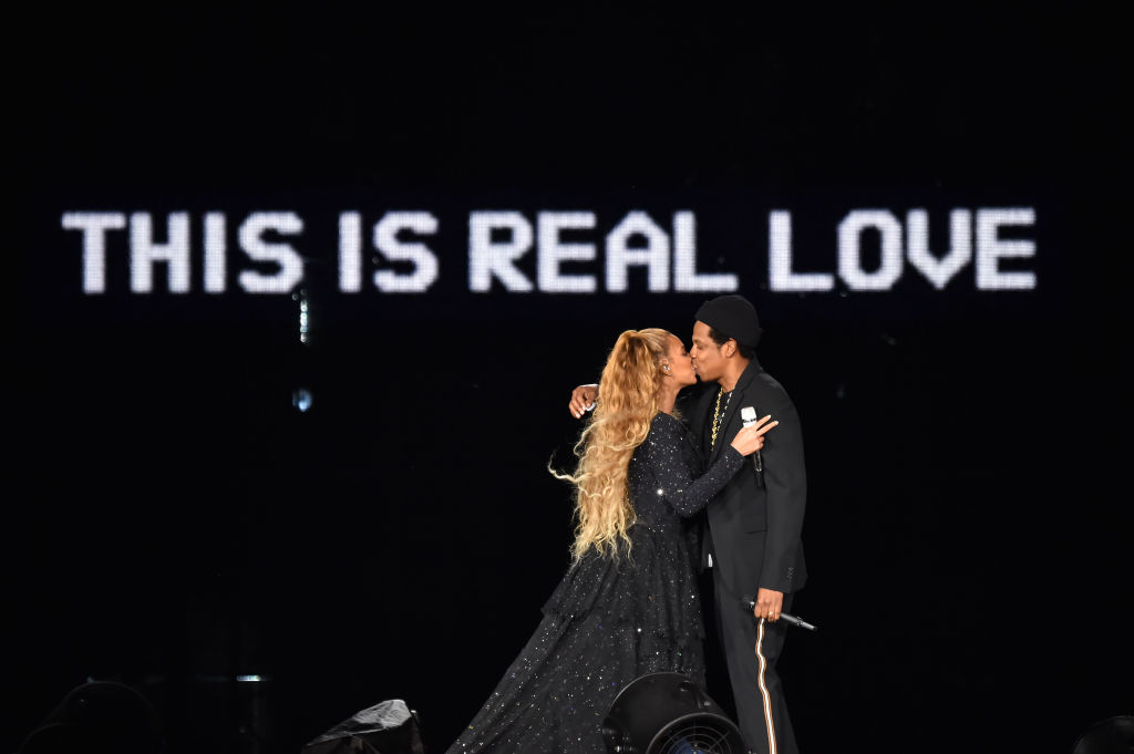 Beyoncé and Jay-Z kissing on stage in front of a background that says 'THIS IS REAL LOVE'