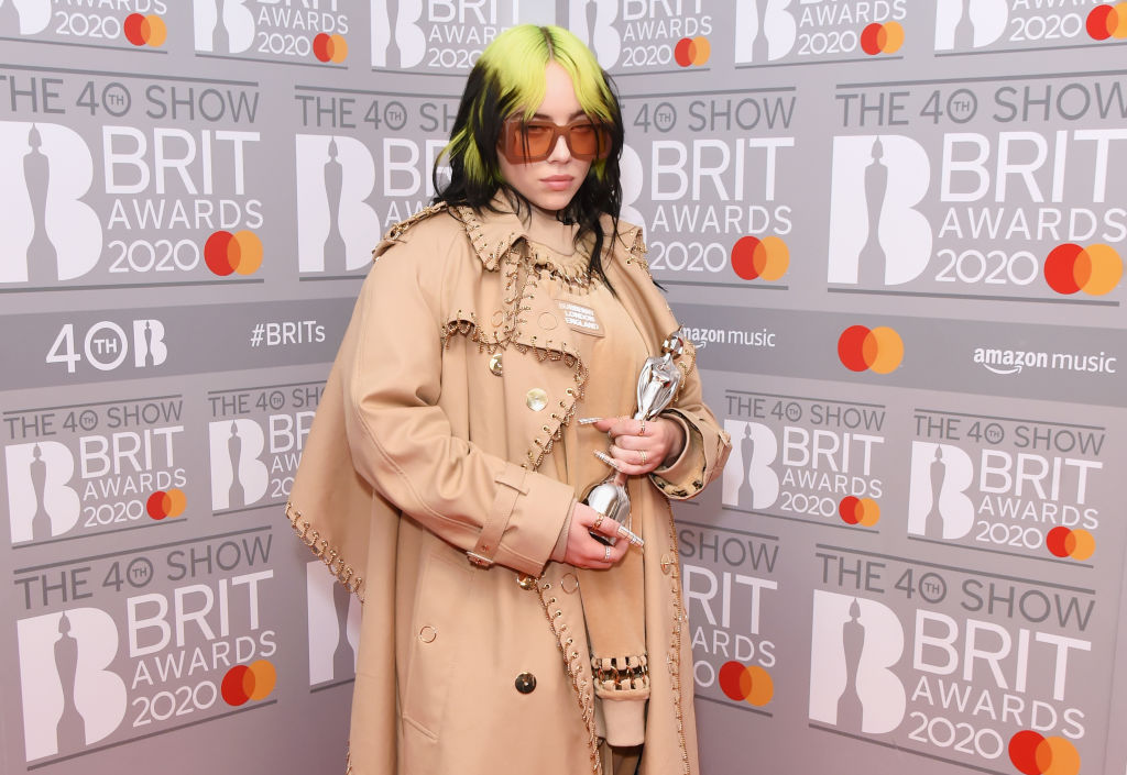 Billie Eilish wearing sunglasses, holding an award in front of a repeating background