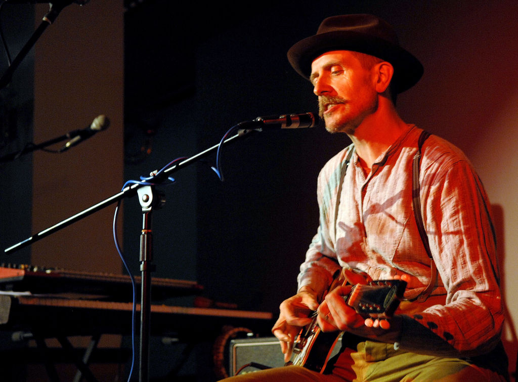 Billy Childish sitting, wearing a fedora, playing a guitar and singing into a microphone