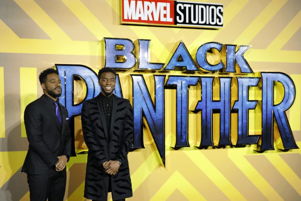 Ryan Coogler and Chadwick Boseman standing in front of a yellow background with a blue 'Black Panther' logo
