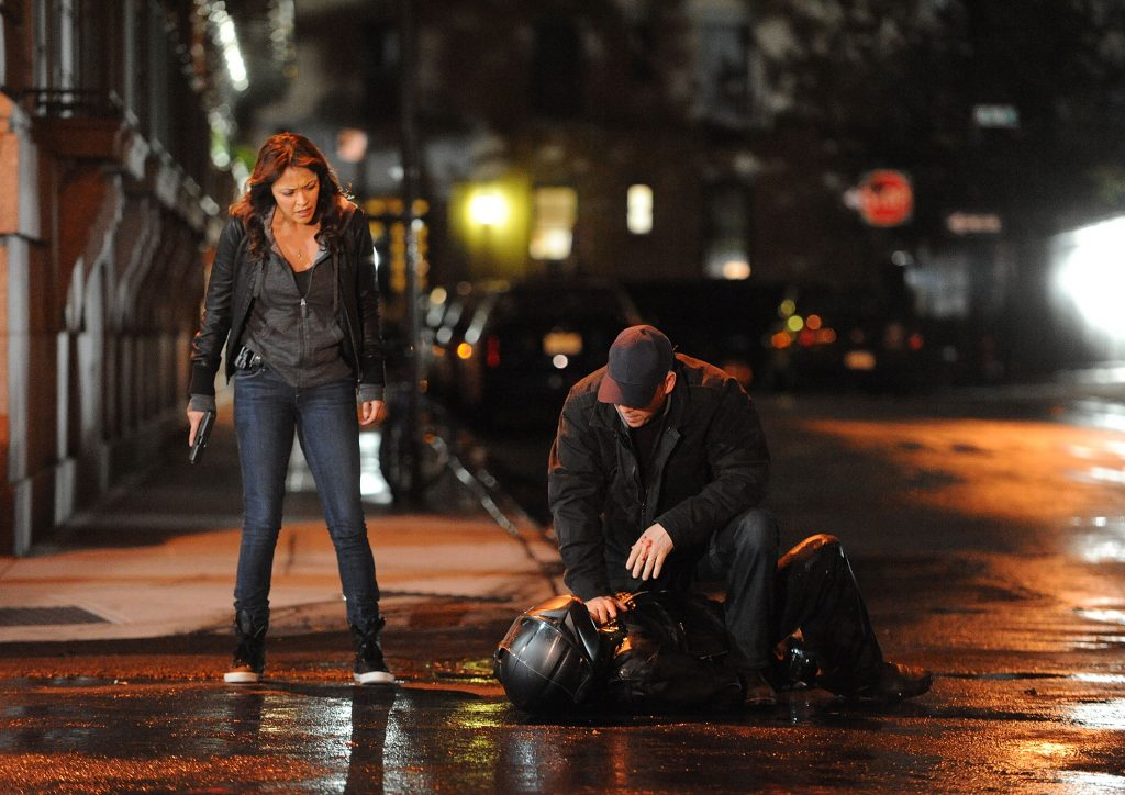 Donnie Wahlberg and Marisa Ramirez on set of 'Blue Bloods' standing in the street over an unconscious person in a helmet