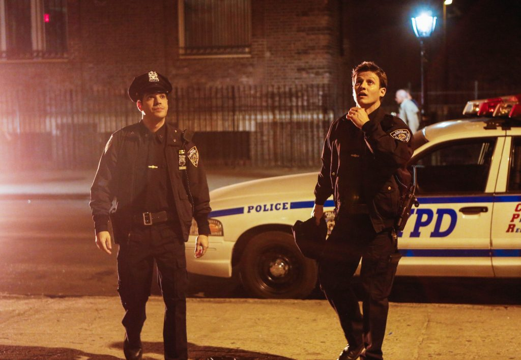 Vinny (left, Sebastian Sozzi) and Jamie (right, Will Estes) standing on the street in police uniform in front of an NYPD car