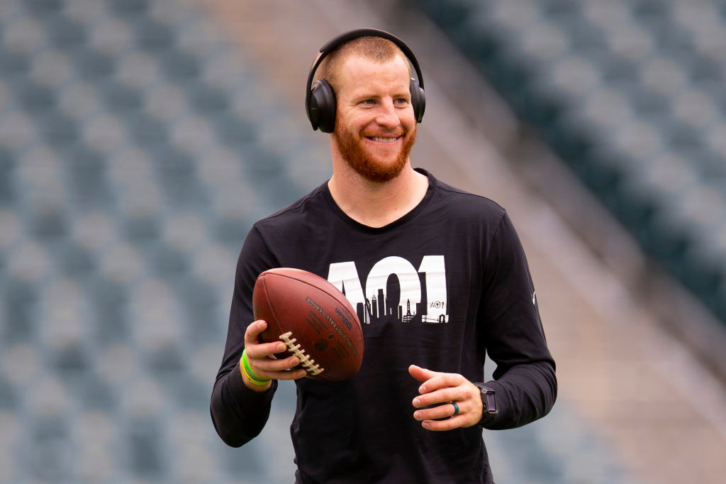 Carson Wentz smiling, holding a football wearing headphones