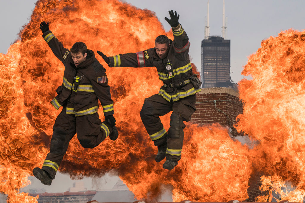 Jesse Spencer as Matthew Casey, Taylor Kinney as Kelly Severide jumping in front of large clouds of fire