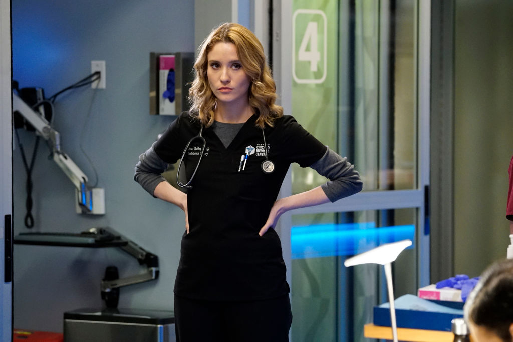 Norma Kuhling as Ava Bekker on 'Chicago Med' standing in scrubs with her hands on her hips in a hospital room