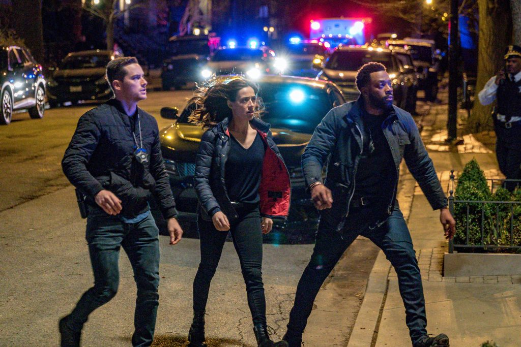 Jesse Lee Soffer as Det. Jay Halstead, Marina Squerciati as Officer Kim Burgess, LaRoyce Hawkins as Officer Kevin Atwater walking outside in front of several police cars with lights on