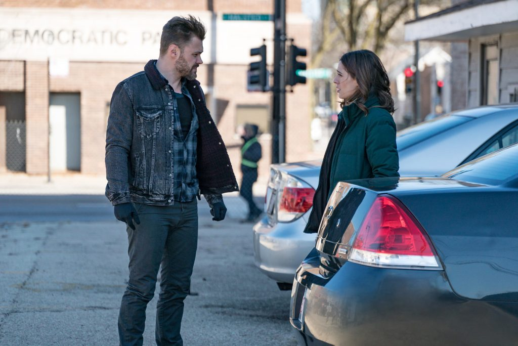 Patrick John Flueger as Adam Ruzek, Marina Squerciati as Kim Burgess turned to the side, facing each other in a parking lot