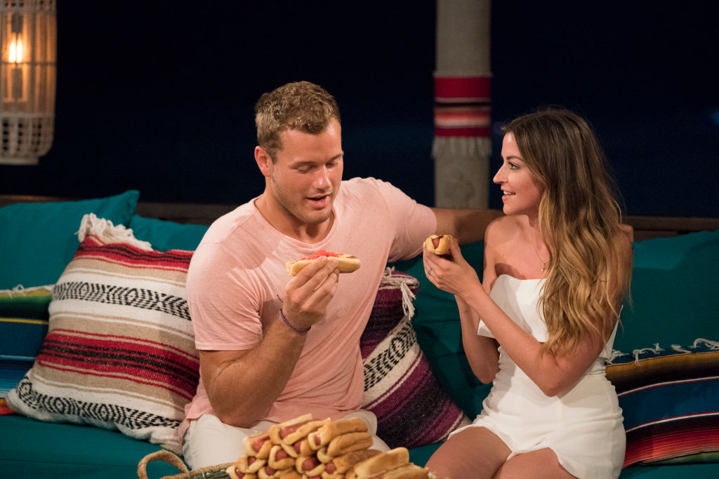 Colton Underwood and Tia Booth with a mound of hot dogs.