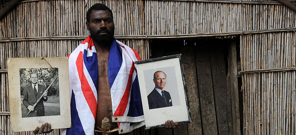 Coorey Sikor Natuan, the son of the local chief, holding portraits of Prince Philip