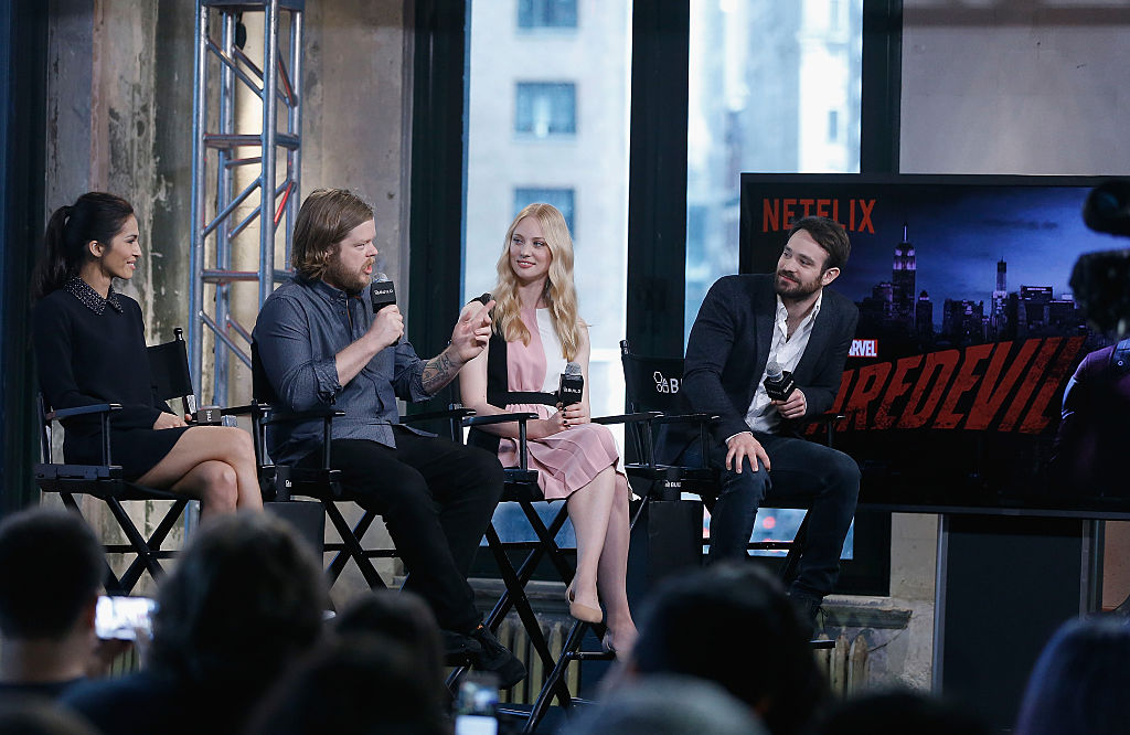 Elodie Yung, Elden Henson, Deborah Ann Woll and Charlie Cox speaking on a stage next to a screen with the 'Daredevil' logo