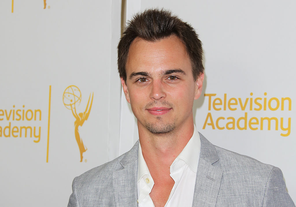 Darin Brooks smiling in front of a white background with a repeating logo