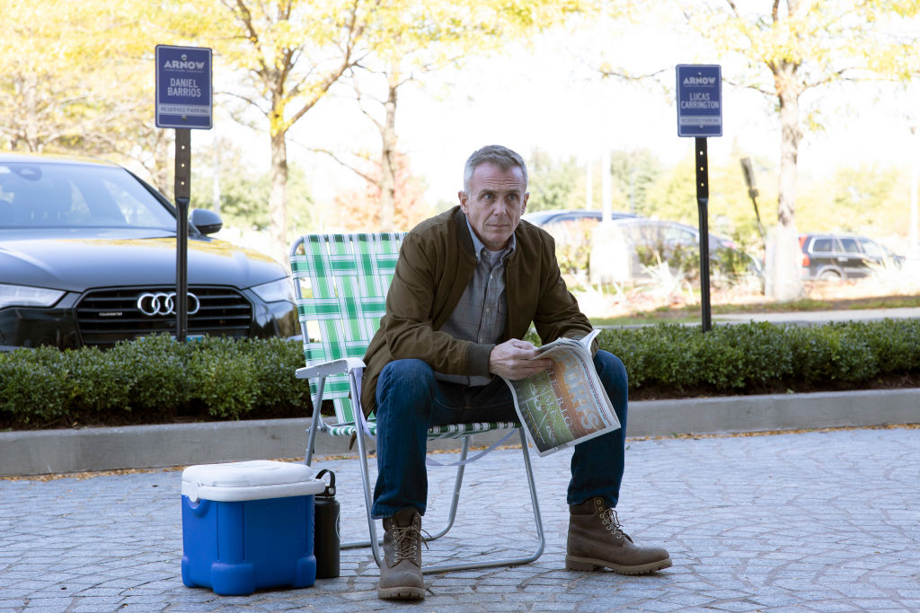 David Eigenberg as Christopher Herrmann sitting in a lawn chair holding a paper, looking off into the distance
