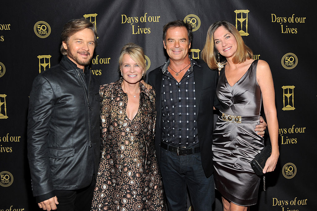 Stephen Nichols, Mary Beth Evans, Wally Kurth, Kassie DePaiva smiling in front of a black backdrop with repeating logo