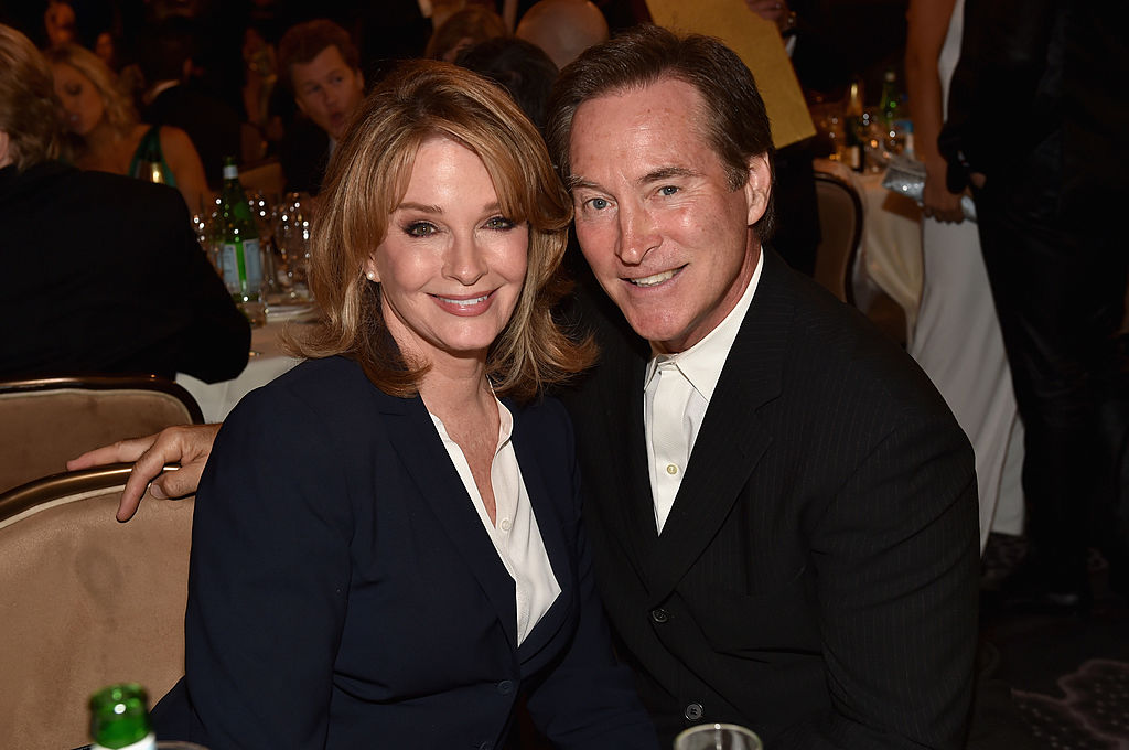 Deidre Hall and Drake Hogestyn smiling, sitting at a dinner table