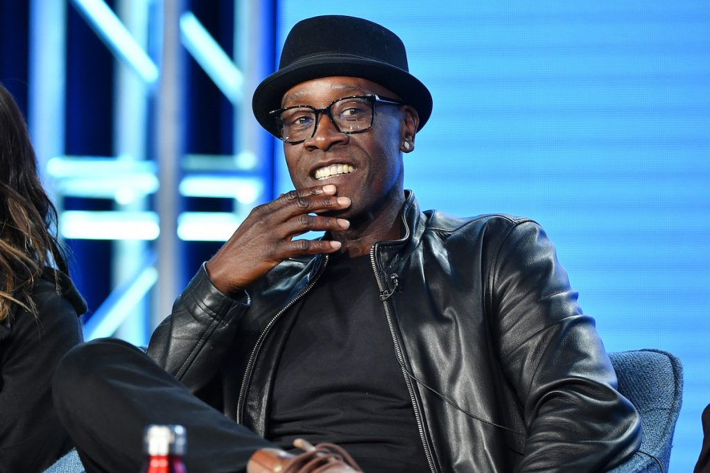 Don Cheadle smiling, looking off to the side, sitting in front of a blue background