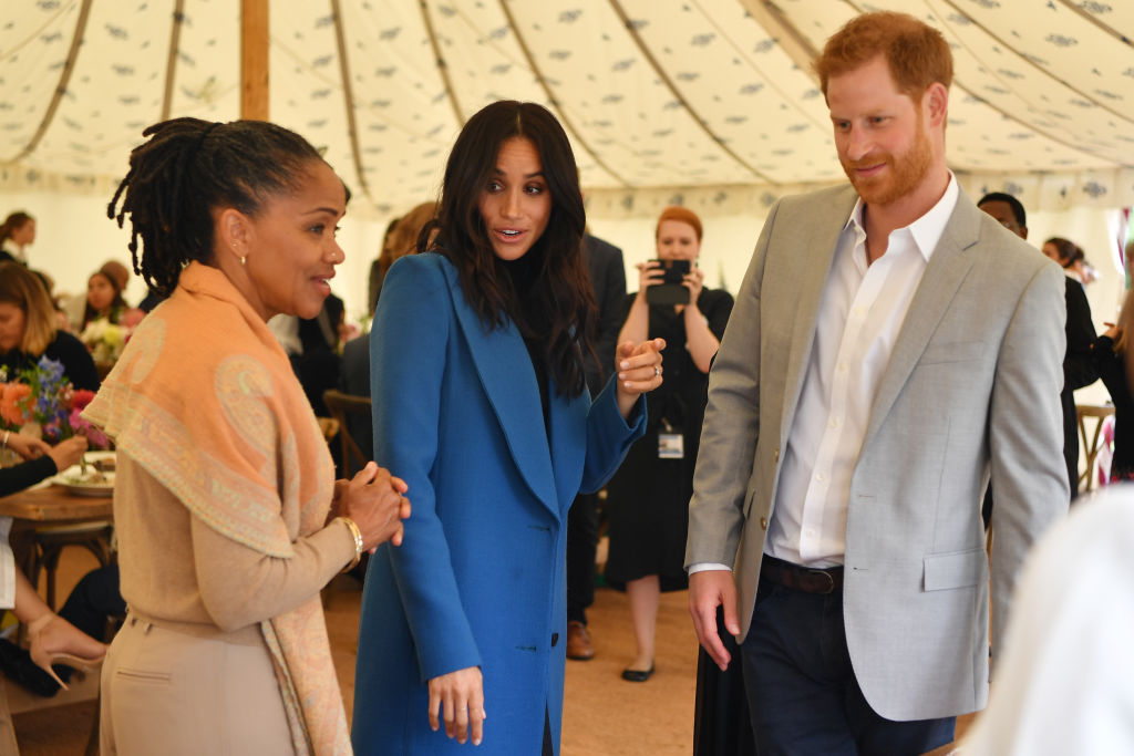 Meghan, Duchess of Sussex (C) arrives with her mother Doria Ragland (L) and Prince Harry, Duke of Sussex to host an event to mark the launch of a cookbook with recipes from a group of women affected by the Grenfell Tower fire at Kensington Palace on September 20, 2018 in London, England