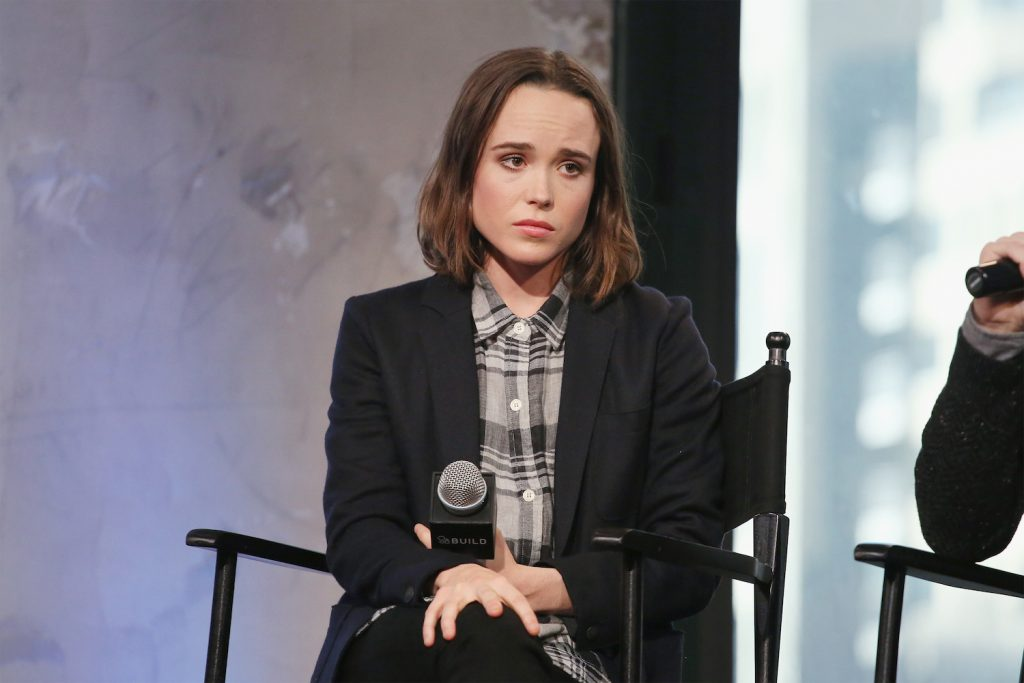 Ellen Page not smiling, looking away from the camera holding a microphone