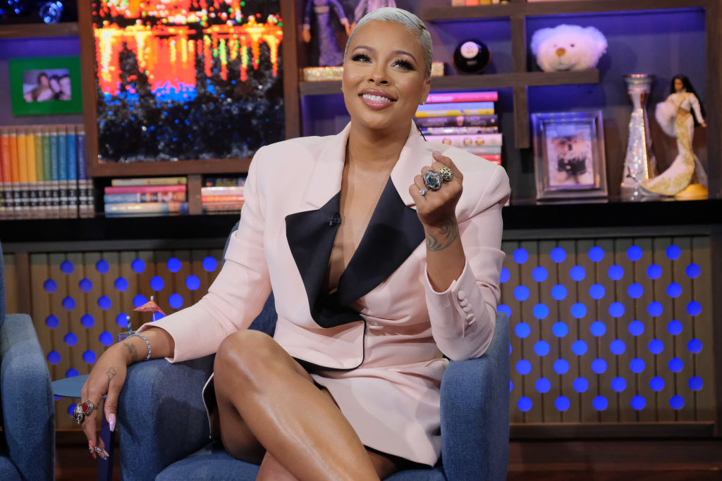 Eva Marcille smiling, sitting in a chair wearing a pink dress