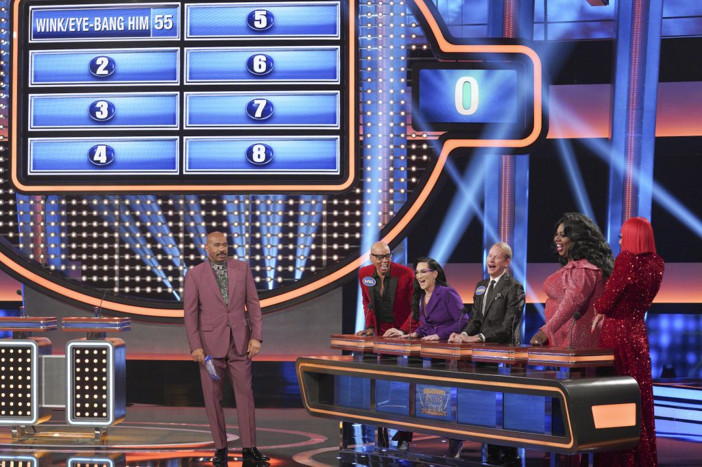 Steve Harvey in front of a Family Feud board next to the cast of RuPauls Drag Race
