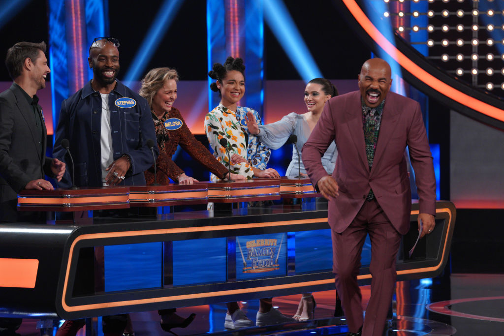 Steve Harvey laughing on stage with cast members of 'The Bold Type' on 'Celebrity Family Feud'