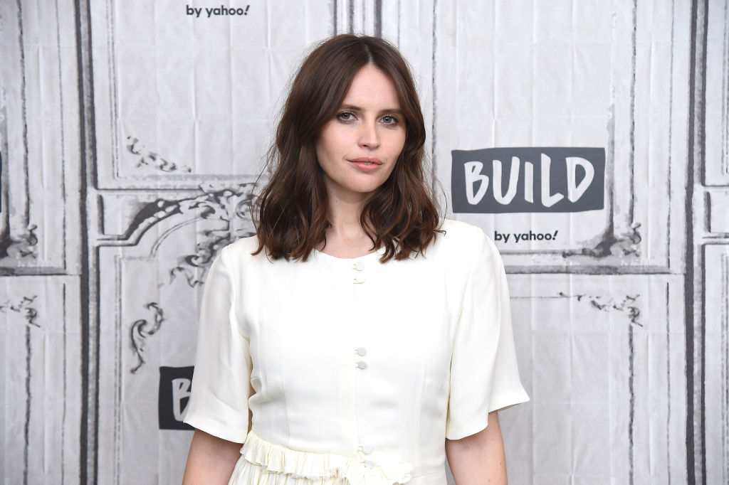 Felicity Jones smiling slightly wearing white