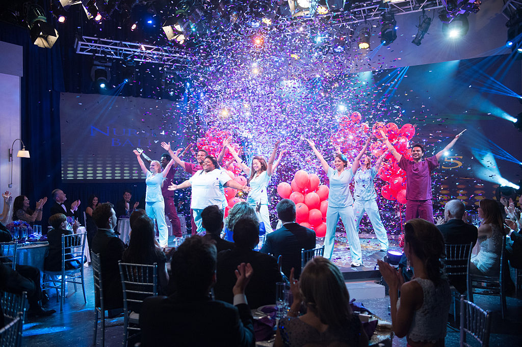 Cast dressed as nurses on stage doing a dance routine while balloons and confetti fall from the ceiling