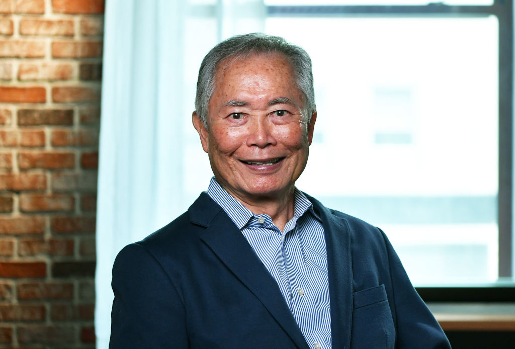 George Takei smiling in front of a window and brick wall