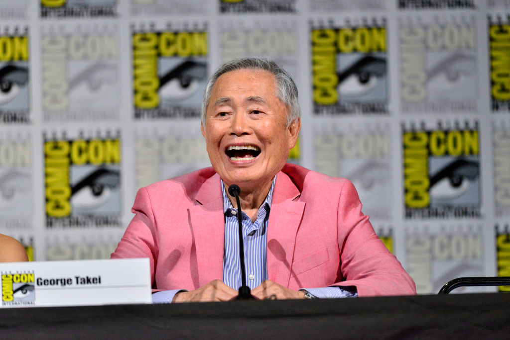 George Takei laughing in front of a repeating background