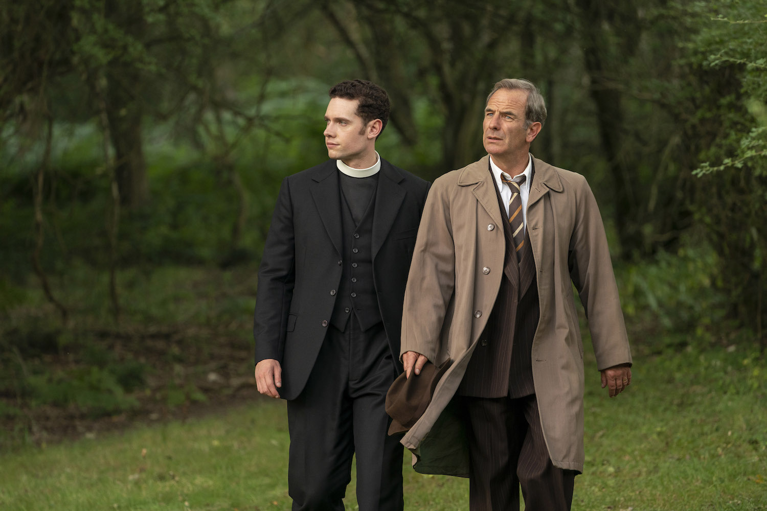 Tom Brittney as Will Davenport, wearing priest's collar, and Robson Green as Geordie Keating, wearing tan jacket, in 'Grantchester'