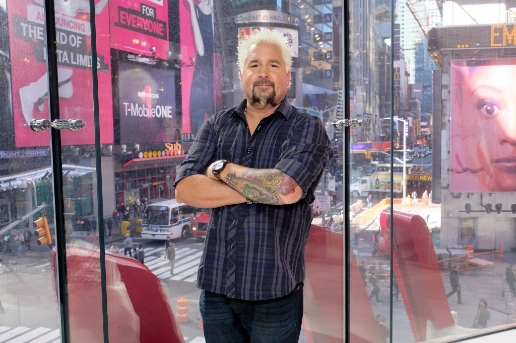 Guy Fieri smiling with his arms crossed in front of a window overlooking Times Square