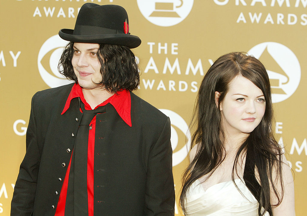 Jack White and Meg White smiling in front of a beige background with a repeating logo