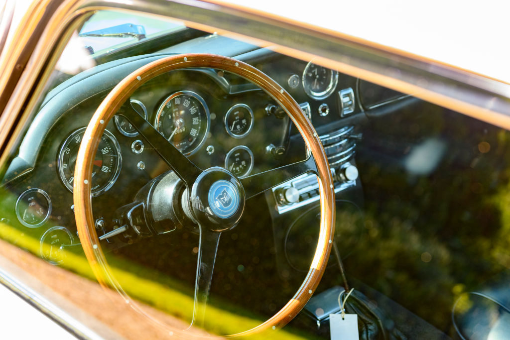 Aston Martin steering wheel photographed through the driver side window