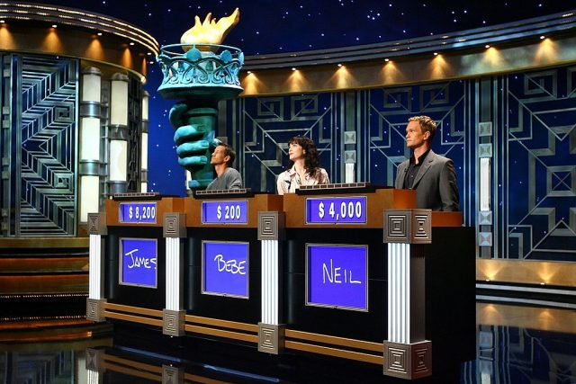 James Denton, Bebe Neuwirth, and Neil Patrick Harris stand at their podiums rehearsing for Celebrity 'Jeopardy!' in 2006