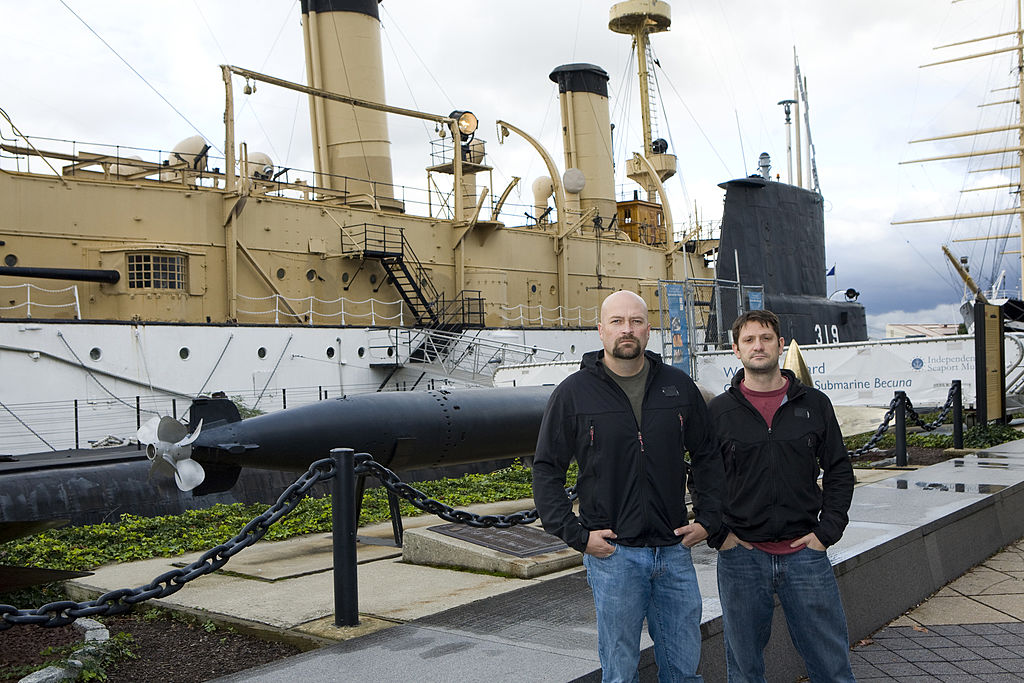 Jason Hawes and Grant Wilson standing in front of a ship